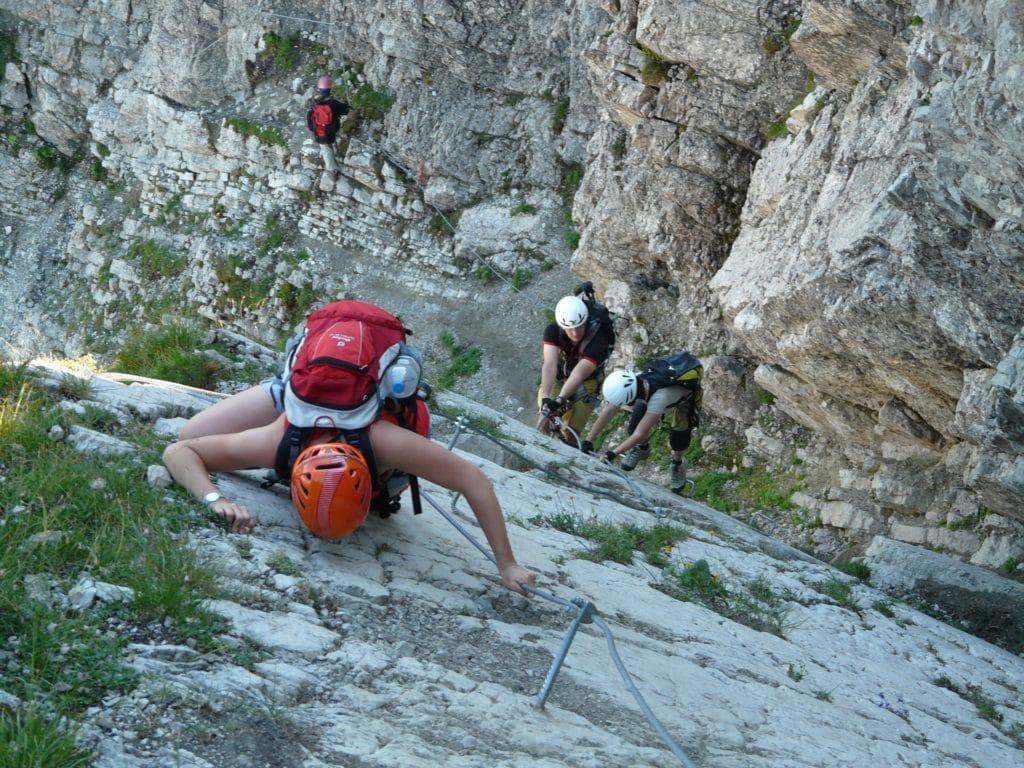 Jugendliche besteigen in Kletterausrüstung gemeinsam einen Berg.