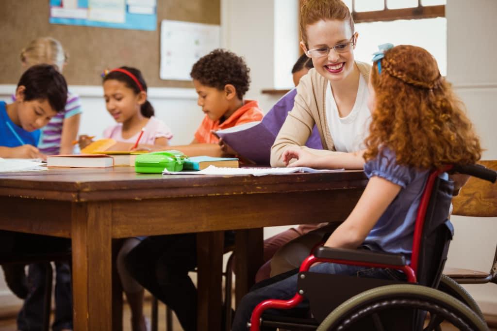 Eine Lehrerin sitzt mit einem Mädchen im ROllstuhl am Tisch.