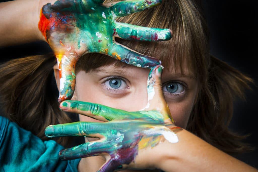Mädchen rahmt, mit ihren Fingern voller Farbe, ihr Auge ein.