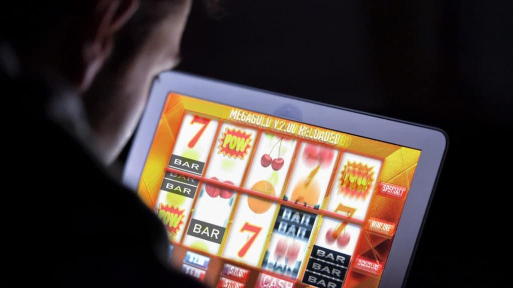 Jemand sitzt nah vor einem Bildschirm, auf dem ein Online Casino zu sehen ist.