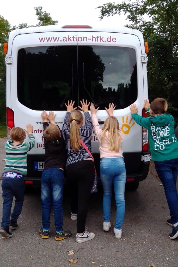 Eine Guppe Kinder schieben einen Bus von hinten an.
