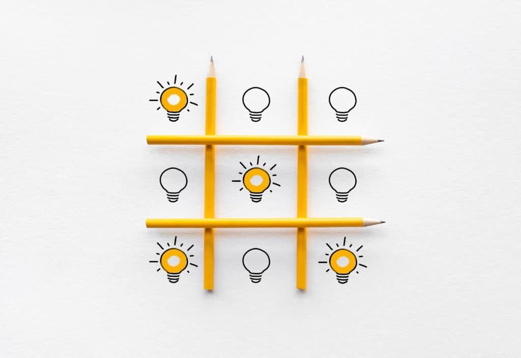 Tic-Tac-Toe Spiel wird anstelle mit Kreuzen und Kreisen mit Glühbirnen gespielt. 3 diagonale Glühbirnen leuchten.