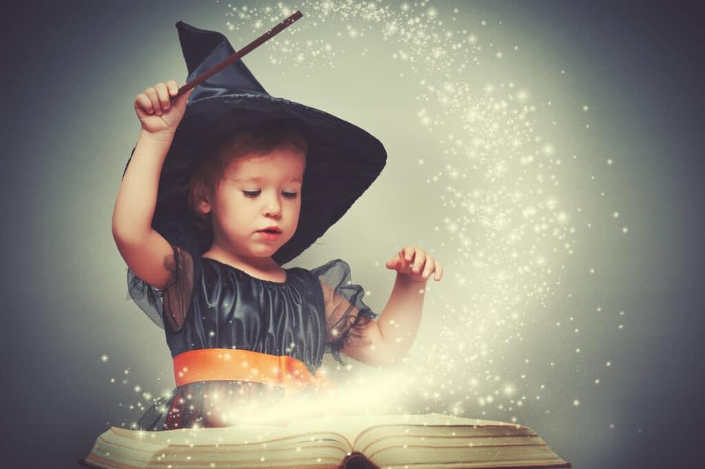 Ein Mädchen trägt einen Zauberhut, sieht auf ein vor ihr liegendes Buch und zaubert. Glitzer verteilt sich als Sie die Zauberstab schwingt.