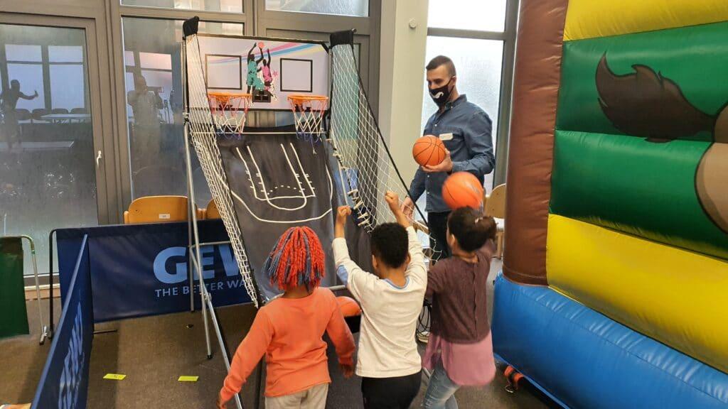 Kinder spielen ein Basketball-Spiel unter Aufsicht eines Mitarbeiters.
