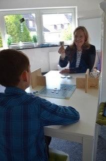 Ein Kind bekommt Förderunterricht von einer Frau hinter einer Glasscheibe.