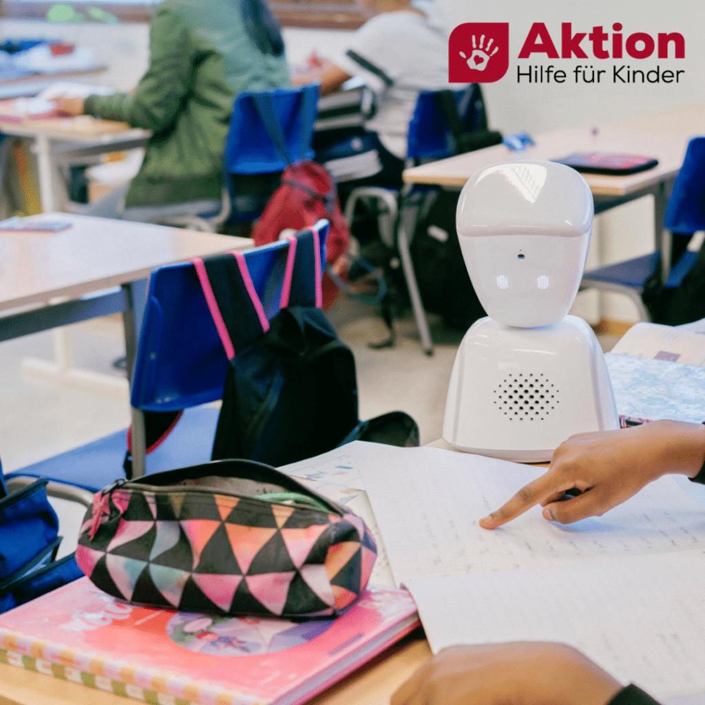 Der Lernroboter sitzt am Tisch und lässt sich von ein/e Schüler*in eine Aufgabe erklären.