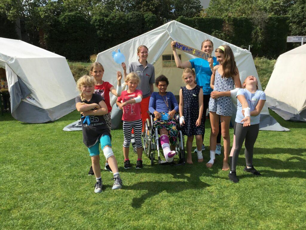 """Eine Gruppe stehen vor einem Zelt, dass das Krankenhaus der Kinderstadt sein soll, bei """"Bremopolis"""" und tragen Verbände."""