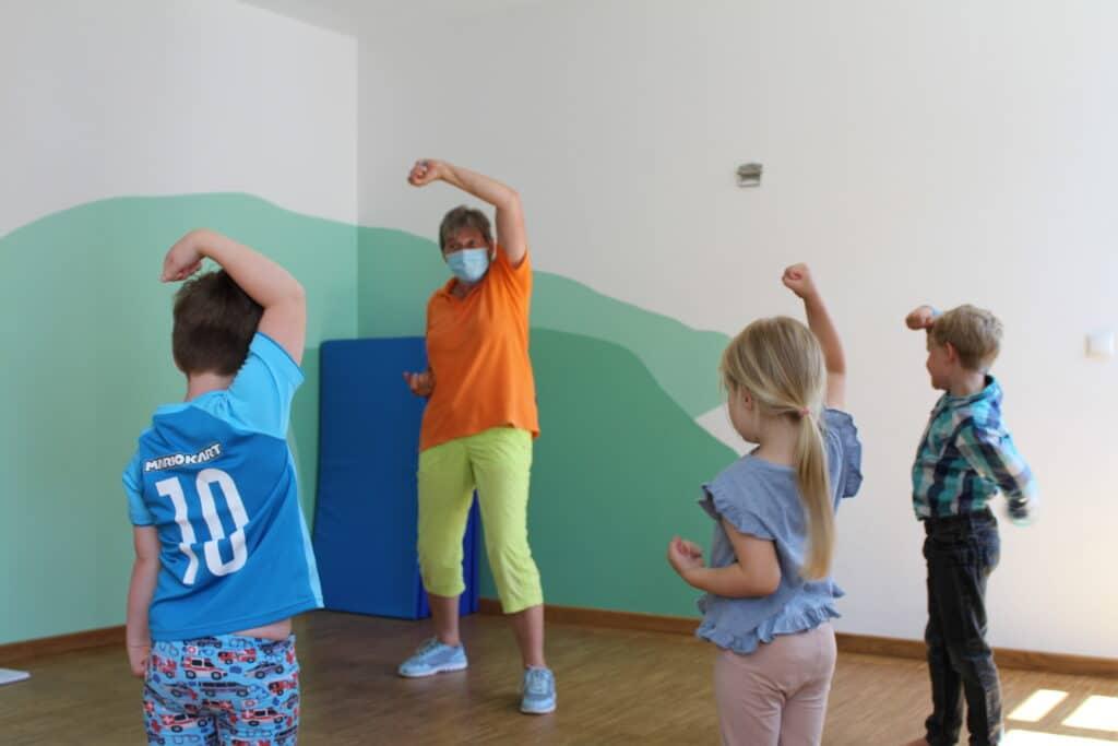 Kinder stehen vor der Selbstbehauptungstrainerin im Halbkreis und reißen abwehrend die Arme hoch.