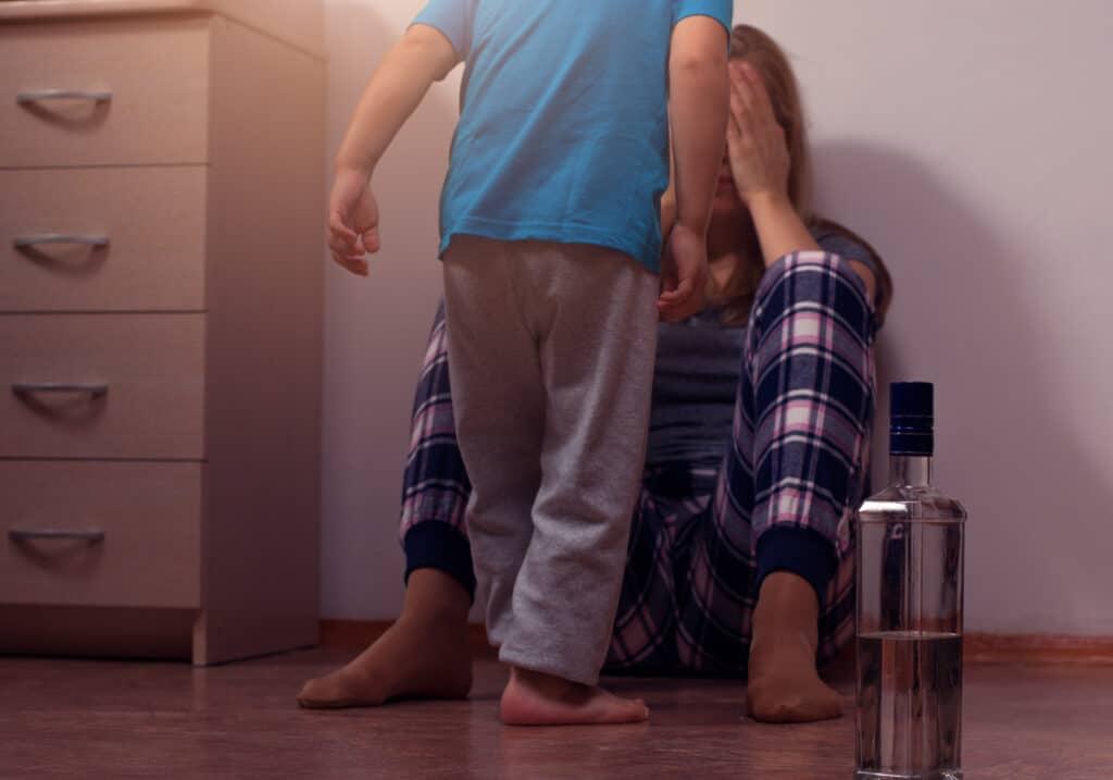 Kind steht vor einer sitzenden Frau, die mit ihren Händen ihr Gesicht verdeckt. neben ihr steht eine Glasflasche mit einer klaren Flüssigkeit.